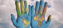 Two hands with world map painted on them